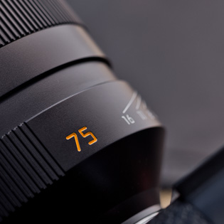 Focal length marking  In recent years, all Leica lenses have gotten an orange marking on the barrel with the focal length so the user can see which lens is mounted on the camera. In this case a 75mm lens.