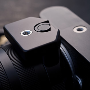 Tripod accessory for Noctilux  To make a perfect balance of camera and lens on a tripod, the tripod accessory is attached to the lens. It further stabilizes the whole set and prevents the lens from being damaged. Leica traditionally always has tripod mounts on larger lenses.