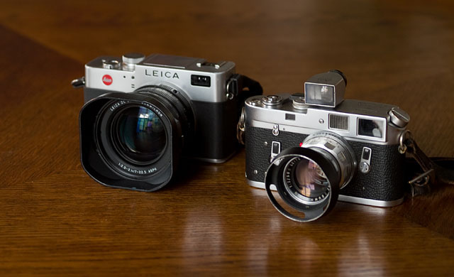 "To the right is the Leica M4 film rangefinder from 1966 with the ""real"" rangefinder mechanism. To the left is the Leica Digilux 2 ""digital rangefinder"" from 2006 that has no direct view through a viewfinder. Where the viewfinder traditionally sits, there is an electronic ""eye"" for the auto focus, and from the other side the user looks through a small (electronic) viewfinder and sees a digital preview of what the camera's sensor sees."