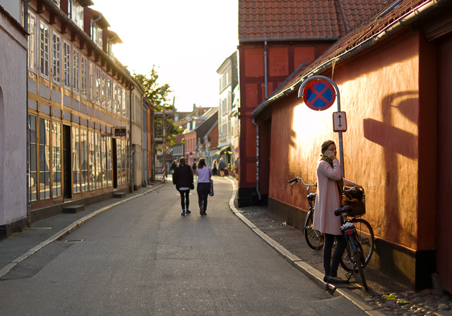 "Perspective is relative position and distance. As here where the girl in front is more than two times taller than the peoplle walking, and 8 times taller than the people in the far background. Also, the parts of the buildings closer to the viewer are ""taller"" than the parts of the same building further away. Late afternoon sun in Denmark. Leica TL2 with Leica 35mm Summilux-TL ASPH f/1.4. © 2017 Thorsten Overgaard."
