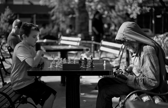 Kid wants to play chess, old man wants to play with his smartphone. Washington Park. Leica M10-P with Leica 50mm Summilux-M ASPH f/1.4. © Thorsten Overgaard.