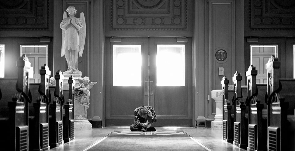 A homeless man's humbled, prostrated prayer inside Saint Ignatius Church in San Francisco. © 2014 Thorsten Overgaard. Leica M 240 with Leica 50mm Noctilux-M ASPH f/0.95