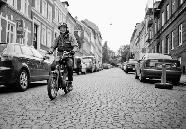A retro-moment as a Danish guy departs for a music festival on his 1970's PUCH Maxi in July 2015. It's actually in Hjemensgade in Aarhus where I used to go to school (the buildings to the right in the picutre).  Leica M 246 with Leica 28mm Summilux-M ASPH f/1.4. © 2015 Thorsten Overgaard.