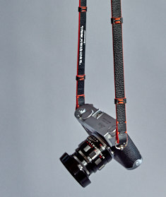 "125cm x 15mm x 3mm Black Calfskin Camera Strap with stubs and orange edges. Inscription on the inside, ""Always Wear A Camera""."